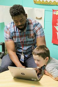 african american young adult helps caucasian boy on a computer