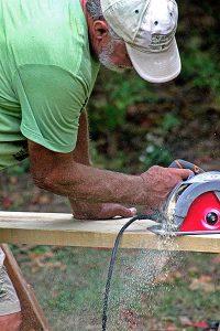 man cutting a board with a circular saw