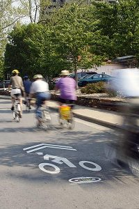several bike riders blurred as they ride by on a city street